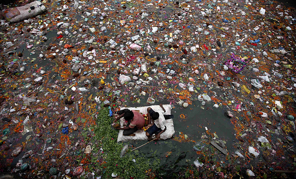 Fishermen search for offerings thrown in by worshippers in the polluted waters of the river Sabarmati in Ahmedabad