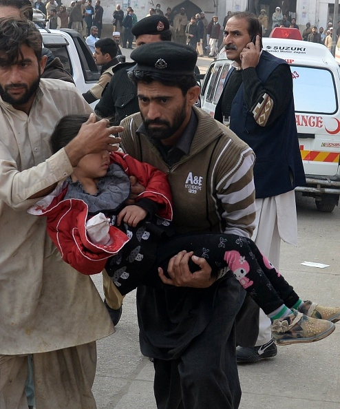 pakistan-taliban-peshawar-pakistani-men-carry-an-injured-school-girl-to-a-hospital-following-an-attack-by-taliban-gunmen-on-a-school-in-peshawar-on-december-16-2014